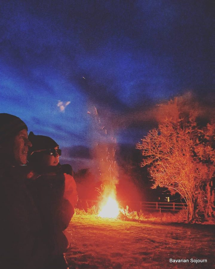 Bonfire night UK, father and young child standing watching fireworks with bonfire in background